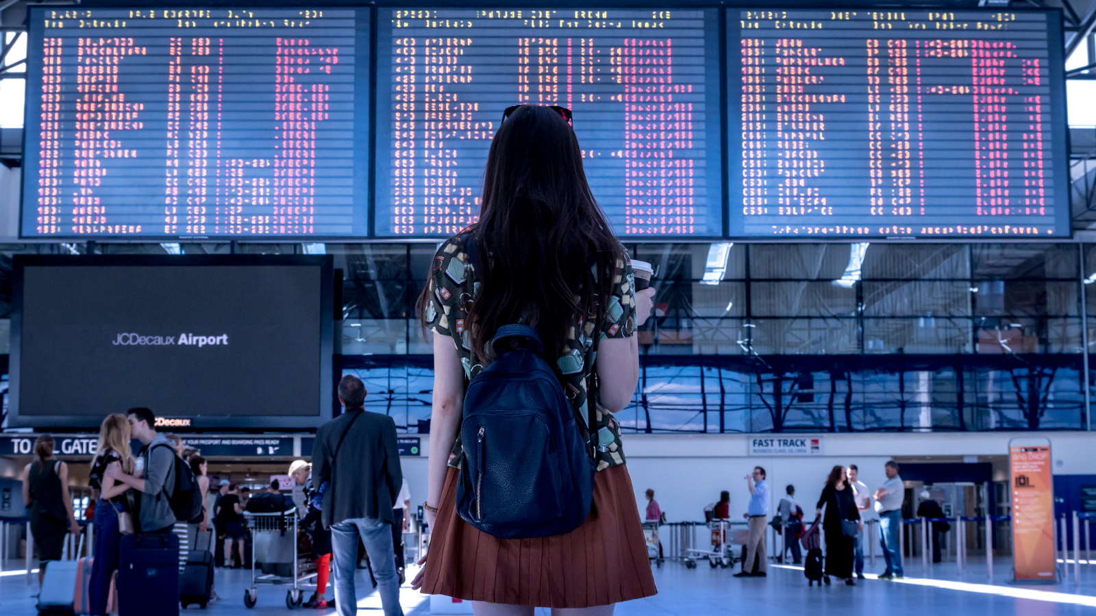 woman looking at flight boarding times in an airport