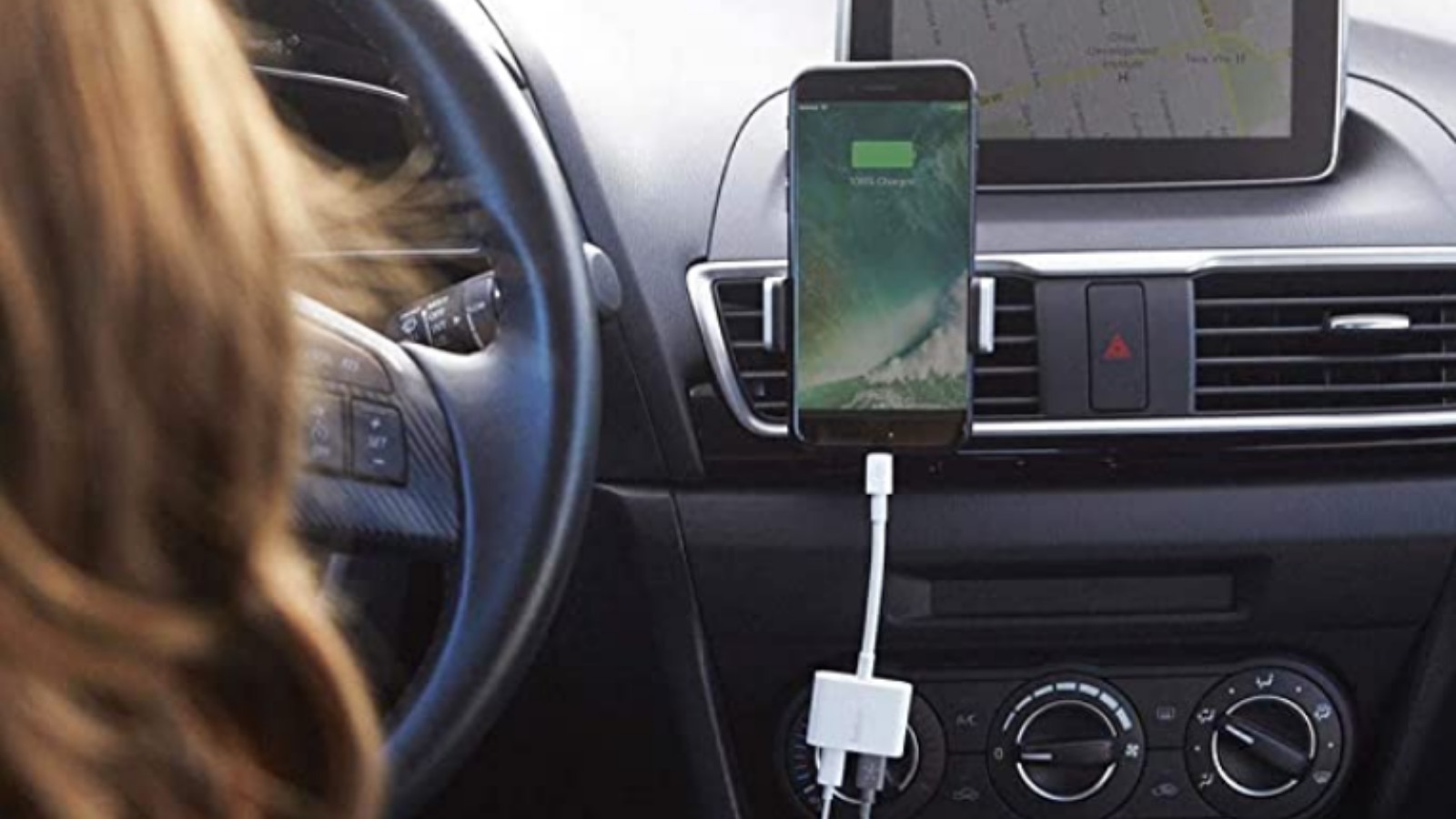 person charging their phone and listening to music in the car with the Belkin Rockstar Adapter