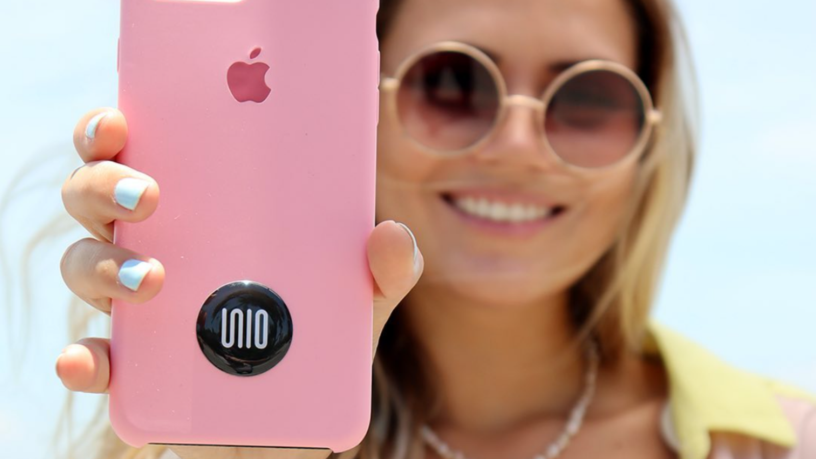 closeup of a woman with sunglasses holding her phone with a Unio attached up to camera