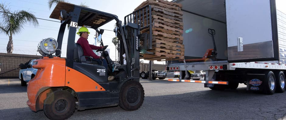 worker putting pallets into big rig truck