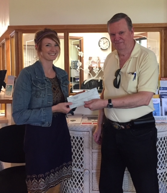 A man and a woman holding a donation check.