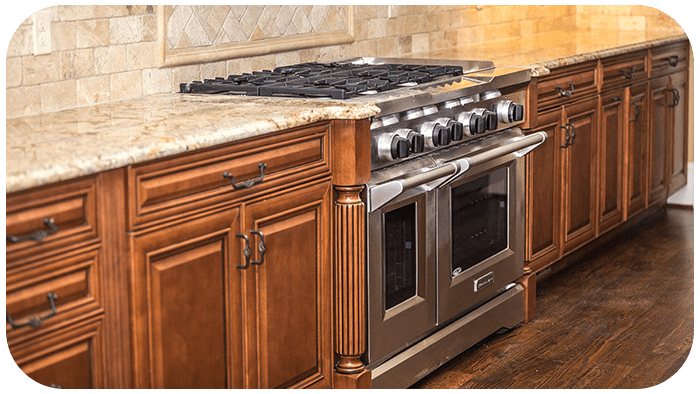 A picture of a beautiful kitchen with a natural gas burning stove.
