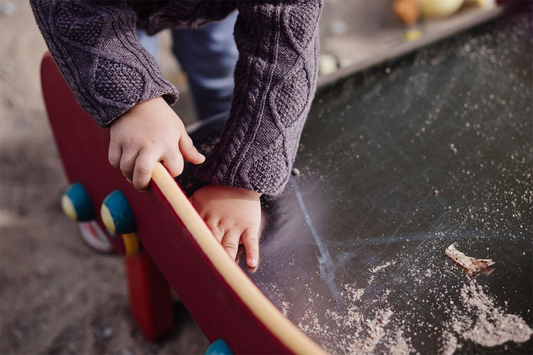 Pest control policies and procedures cover indoor and outdoor settings like this sandpit where a child plays in a child care centre