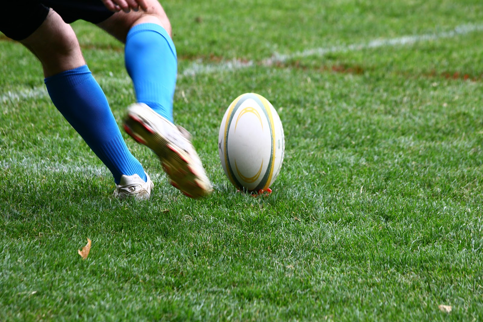 Man kicking a rugby ball on a brightly lit outdoor field where pest control services assess the risk of pest infestations