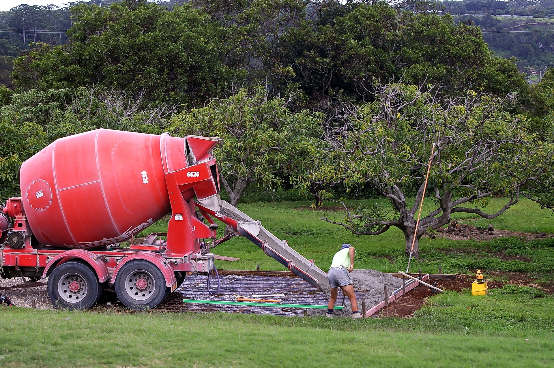 A red cement truck pours concrete with worker spreading the mix after the design and commencement of a termite protection systems.