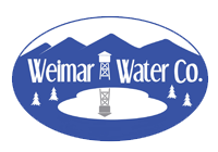 Weimar Water Co. Logo, white on blue, water tower over looking pond against mountain background