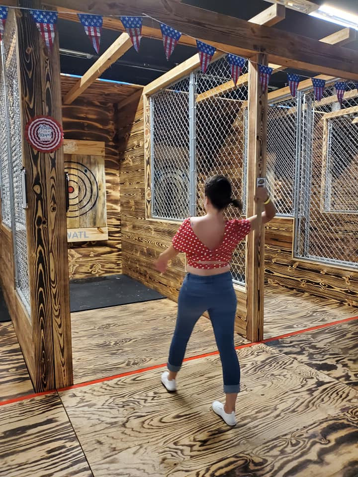 Photo of a young woman throwing and ax towards the target