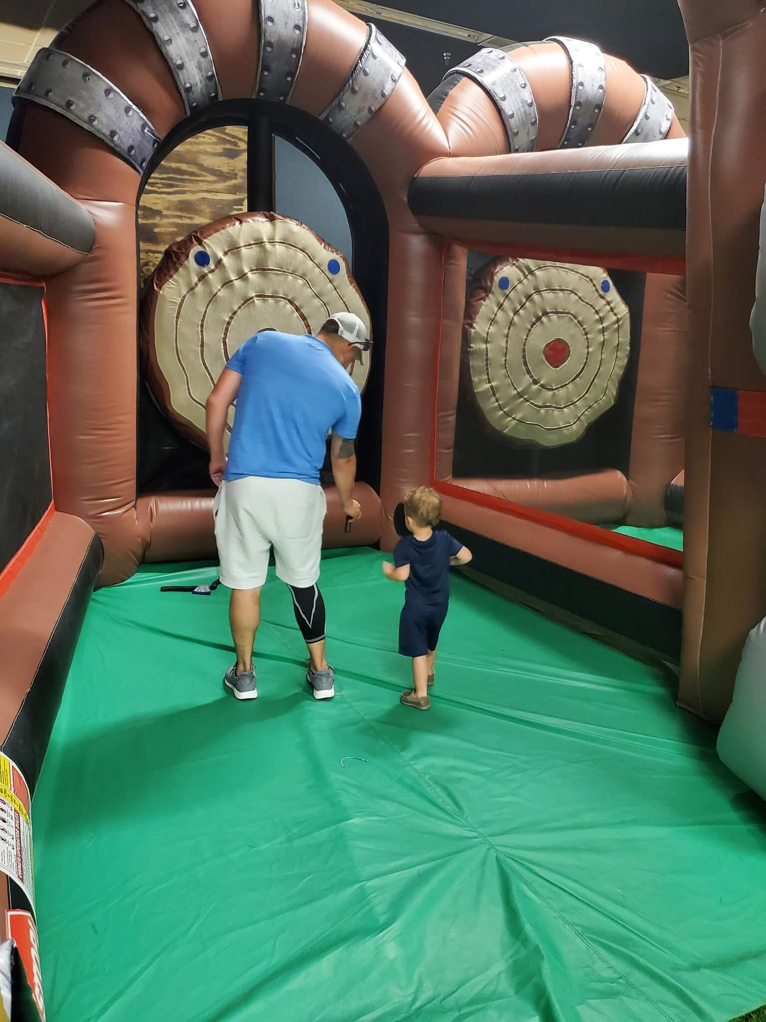 Photo of a man helping a toddler with inflatable ax throwing