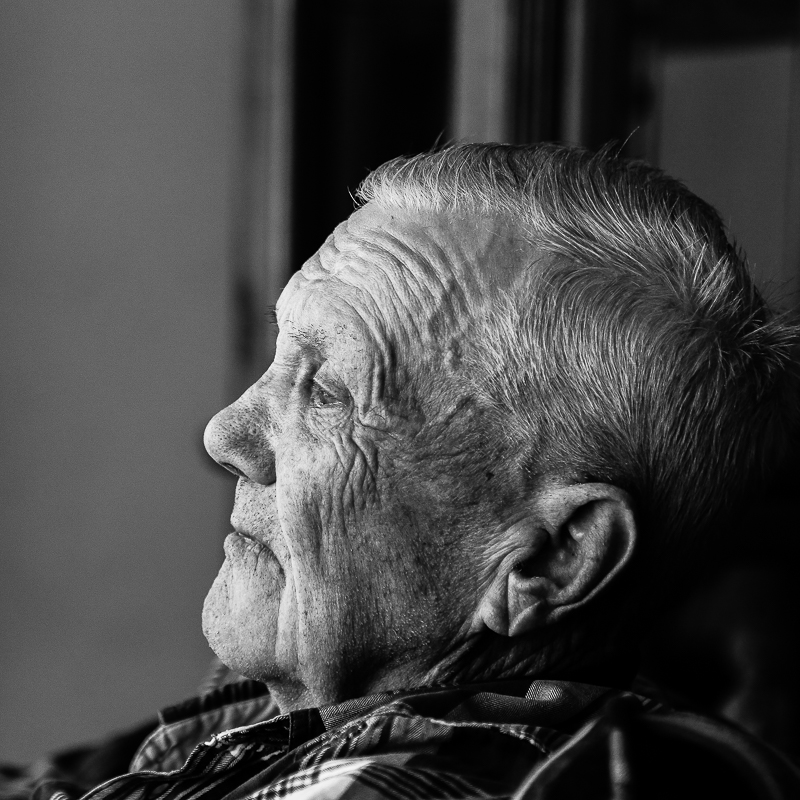 Black and white gallery photo of elderly man looking out the window in his home in Houghton, Michigan.