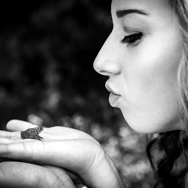 Black and white photo from senior photography session with Natalie Stockel kissing a frog in Walker, Michigan.
