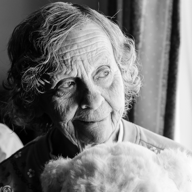 Black and white photograph of elderly woman named Lois Usitalo, who is holding her teddy bear while looking out the window at the Houghton County Medical Care Facility, Hancock, Michigan.