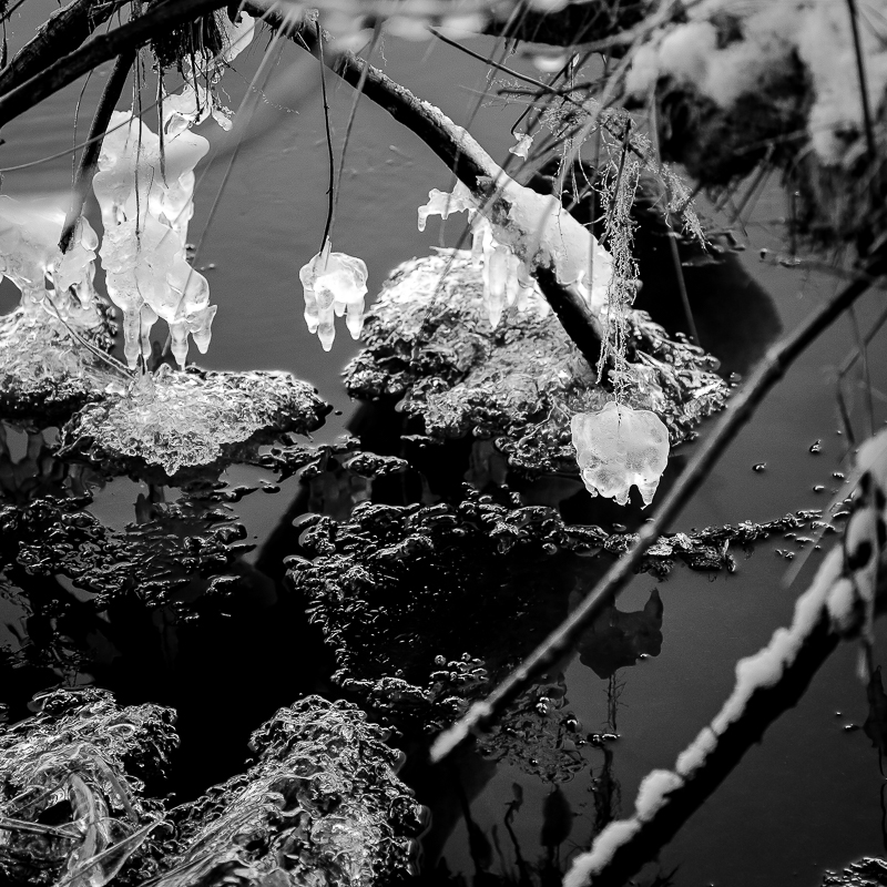 Black and white photograph of ice chandeliers and of water and ice at Misery Bay, located in Toivola, Michigan.