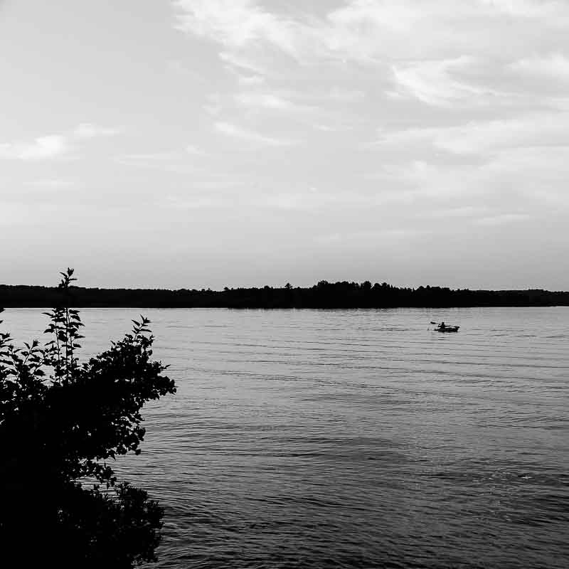 Black and white photography of Lillian Pesola kayaking in the portage canal, in Houghton, Michigan.