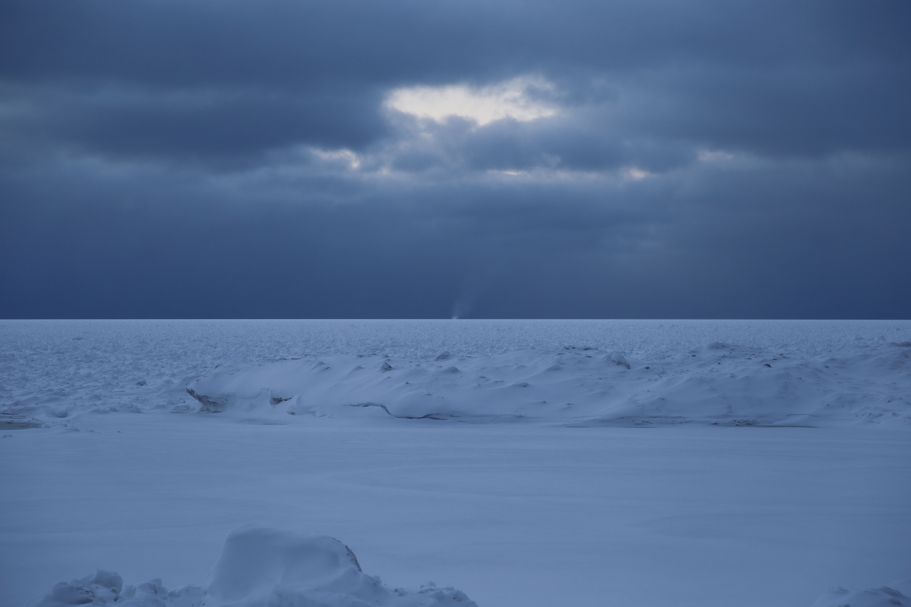 Landscape winter photography of snow, ice, and a snow tornado off in the distance at Agate Beach, located in Toivola, Michigan.