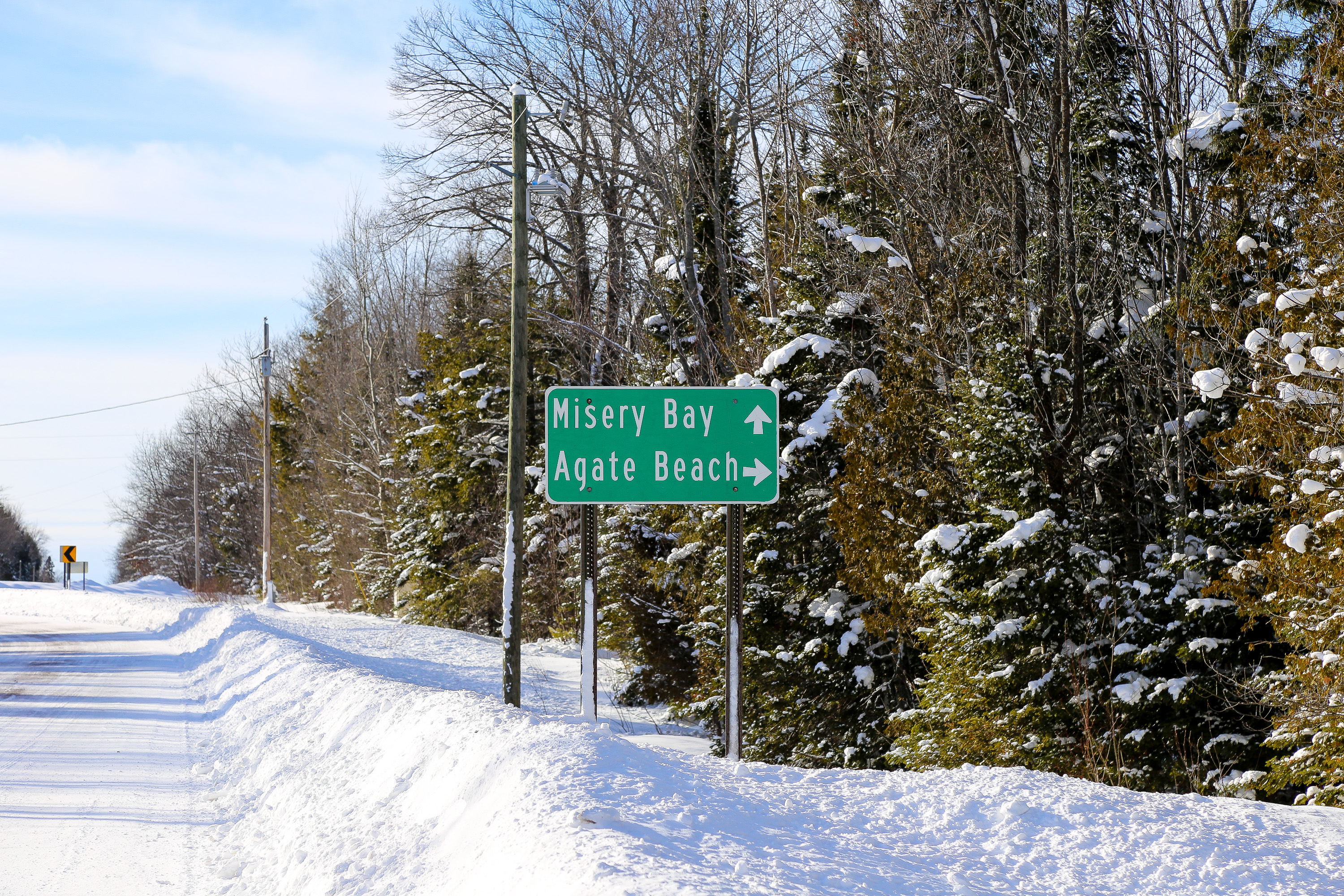 Photograph of the Misery Bay Agate Beach Sign in the winter, located in Toivola, Michigan.