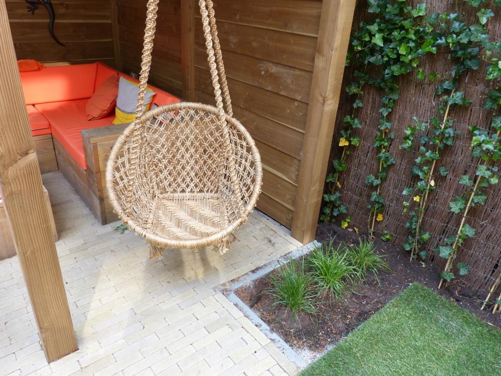 Een hangstoel onder de overkapping voor de ontspanning van de ouders.