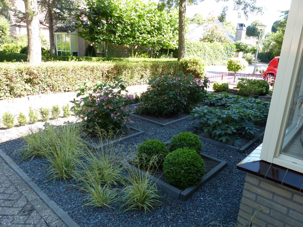 Onderhoudsarme voortuin met split, plantvakken, bloeispreiding, siergrassen en groenblijvende vaste planten.