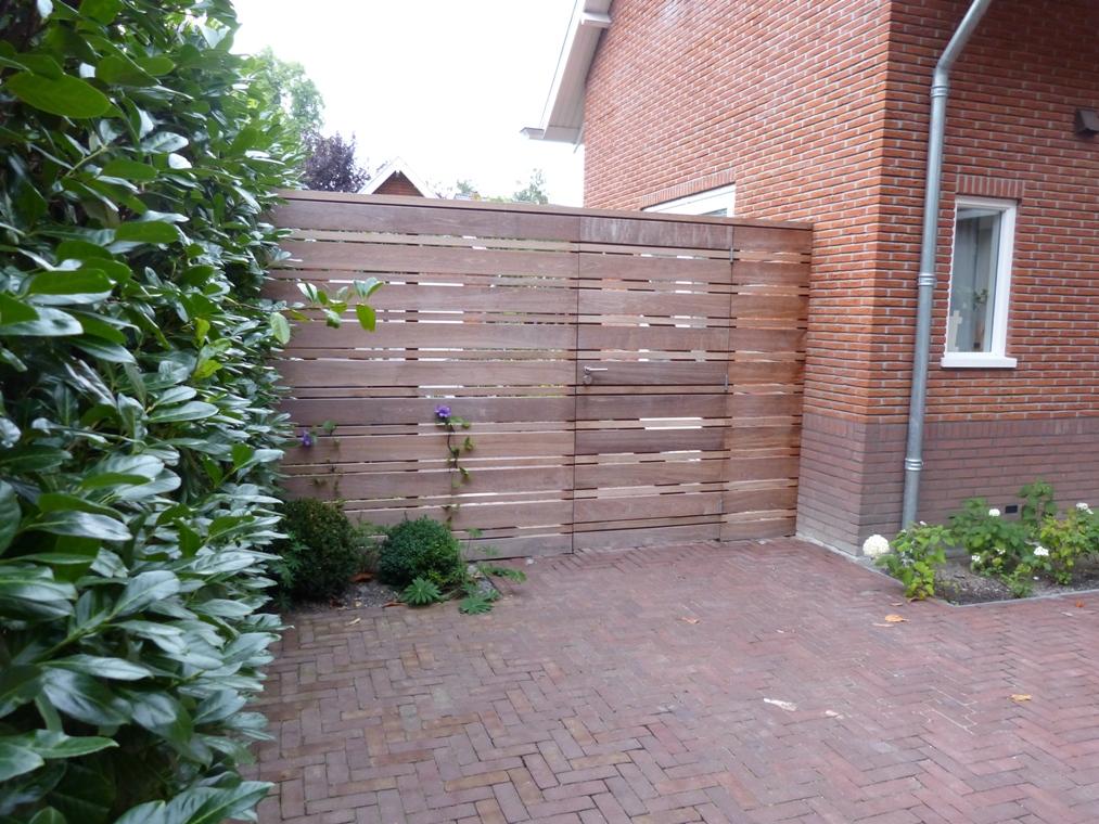 Een semi-transparante poort scheidt dat achtertuin af van de oprit.
