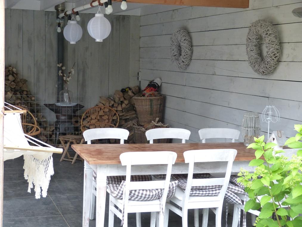 De ruime veranda biest plaatst aan een eethoek, een loungehoek en een buitenkeuken.