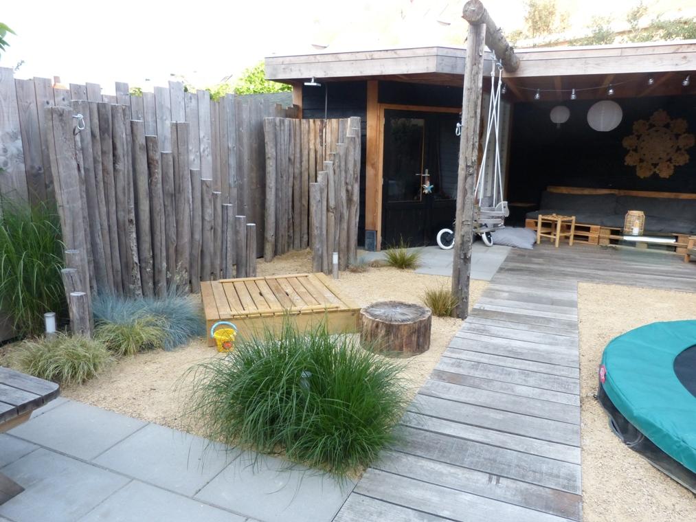 Van verticale ronde palen is een muurtje gemaakt voor de buitendouche.
