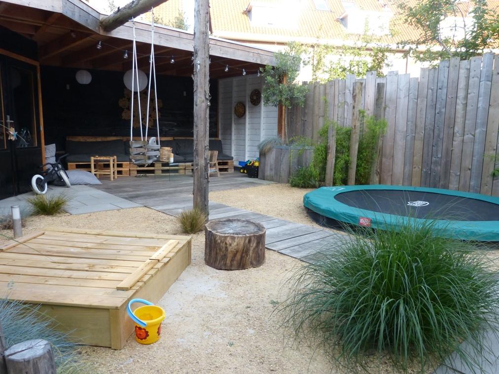 De rubuuste schommel van ronde palen en een ingegraven trampoline moesten zeker terugkomen in de tuin.