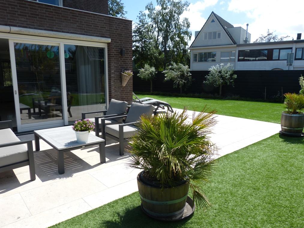 Een natuurstenen terras, veel gras en boompjes voor de zwarte schutting.