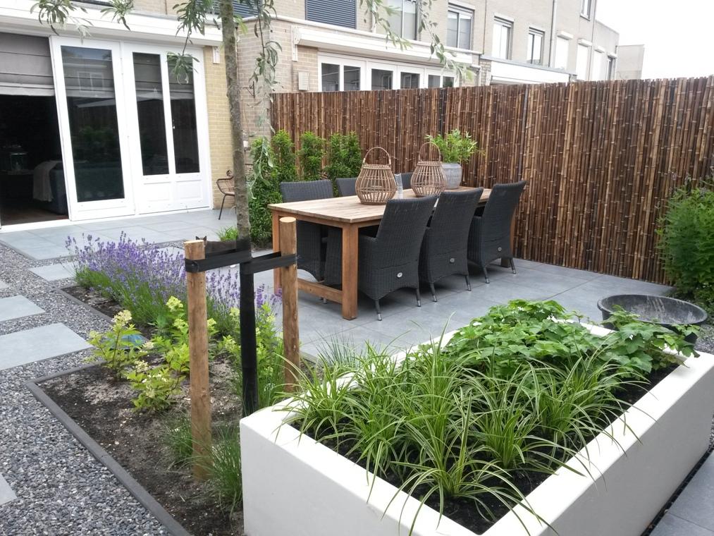 Een stuc-look verhoogde border in deze strakke tuin.