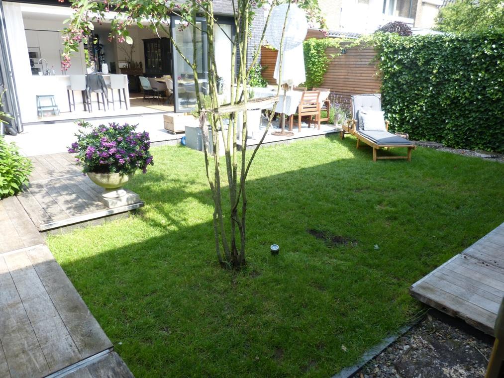 Zicht op de tuin met steenschotten vanuit het tuinhuis.