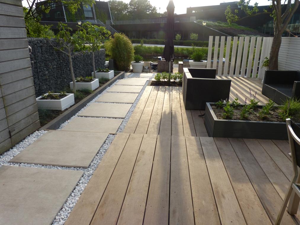 Een hardhouten vlonder met een pad van keramische tegels in wit grind, drie plantenbakken op rij en verticale witte palen.