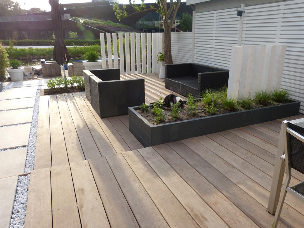 Een grote antraciet maatwerk plantenbak met witte palen op een hardhouten terras.