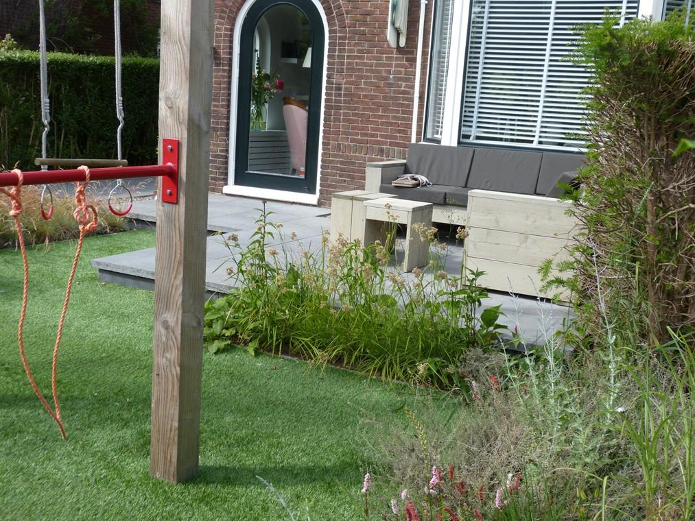 Het speeltoestel in de voortuin, achter het verhoogde terras met loungebank.