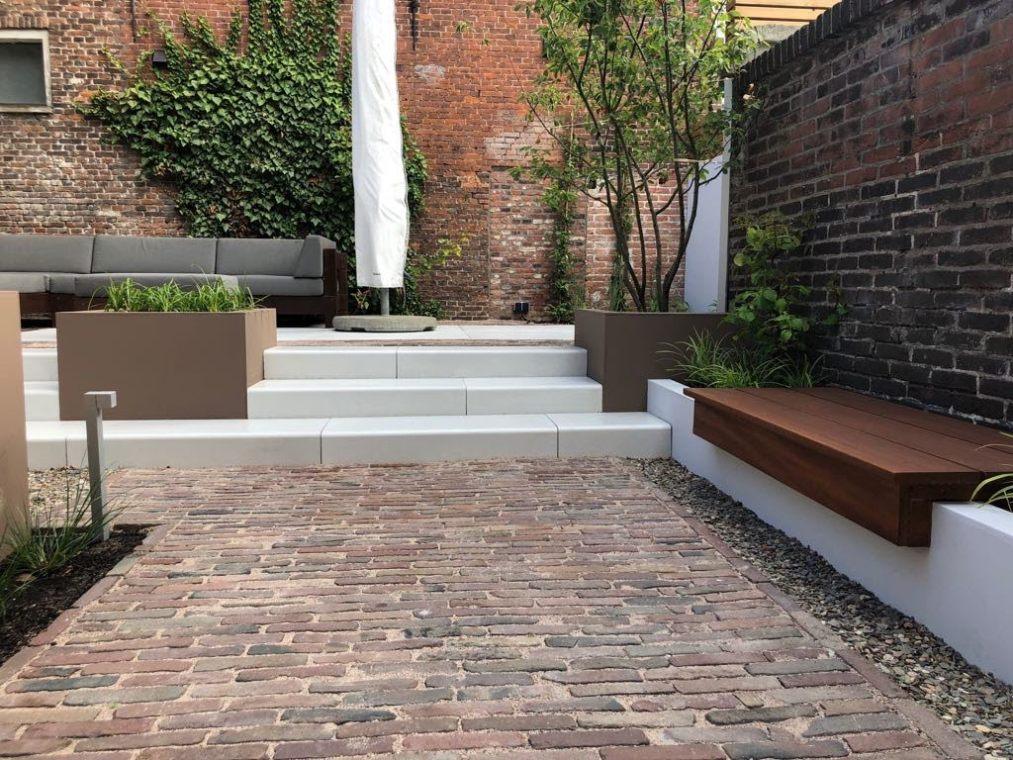 Gebakken klinkers, witte traptreden, bruine muurtjes en plantenbakken en een geïntegreerd tuinbankje in deze stadstuin in Haarlem.