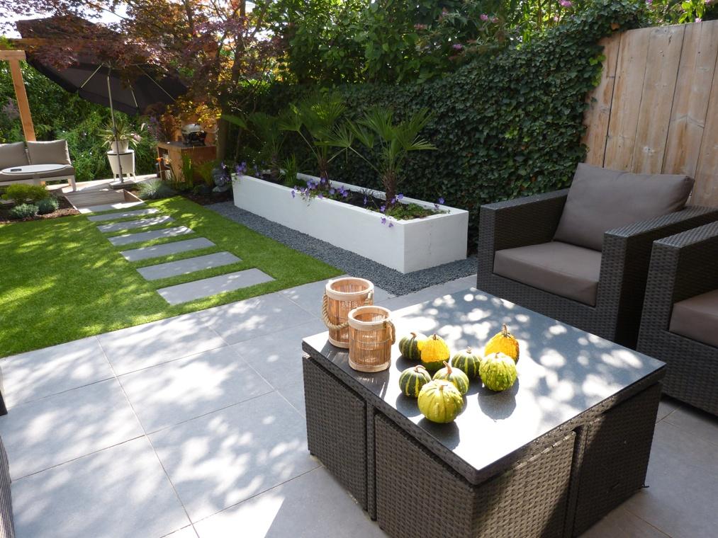 Een terras van keramische tegels, kunstgras, een witte verhoogde border en mediterrane beplanting.