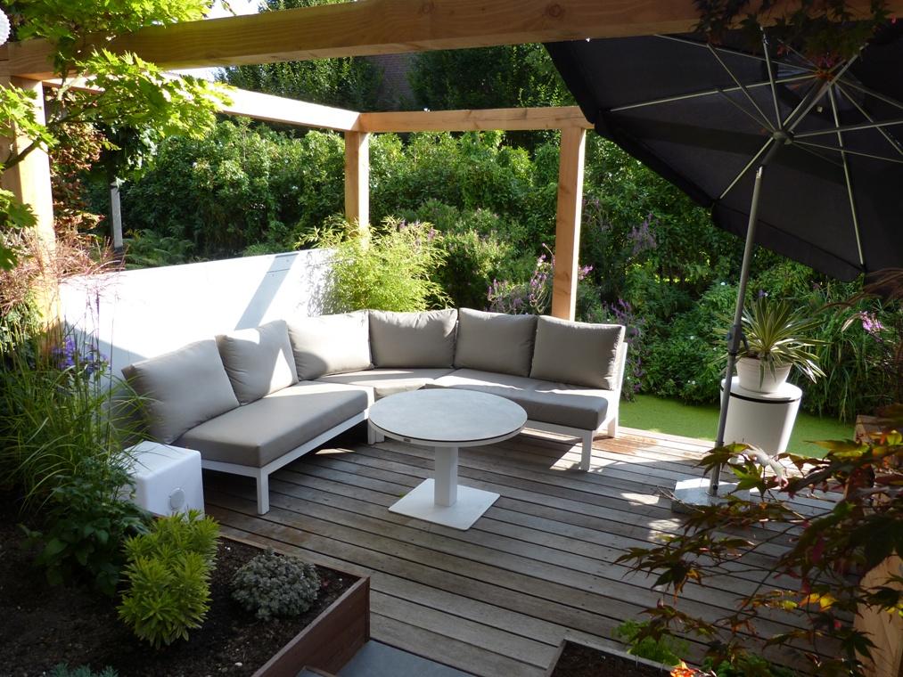 Een ronde loungebank met een in hoogte verstelbare salon - eettafel onder een zelf gebouwd pergola met gestucte muurtjes.