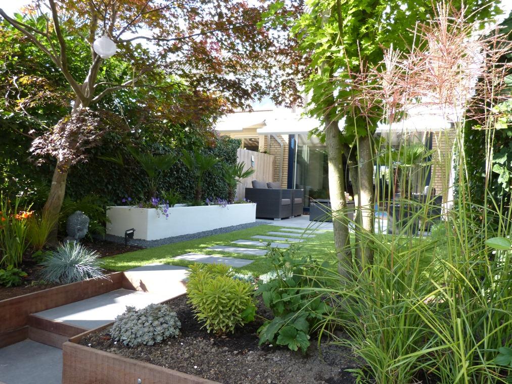 De planken van de hardhouten beschoeiing vormen met de keramische tegels een trap in deze tuin.