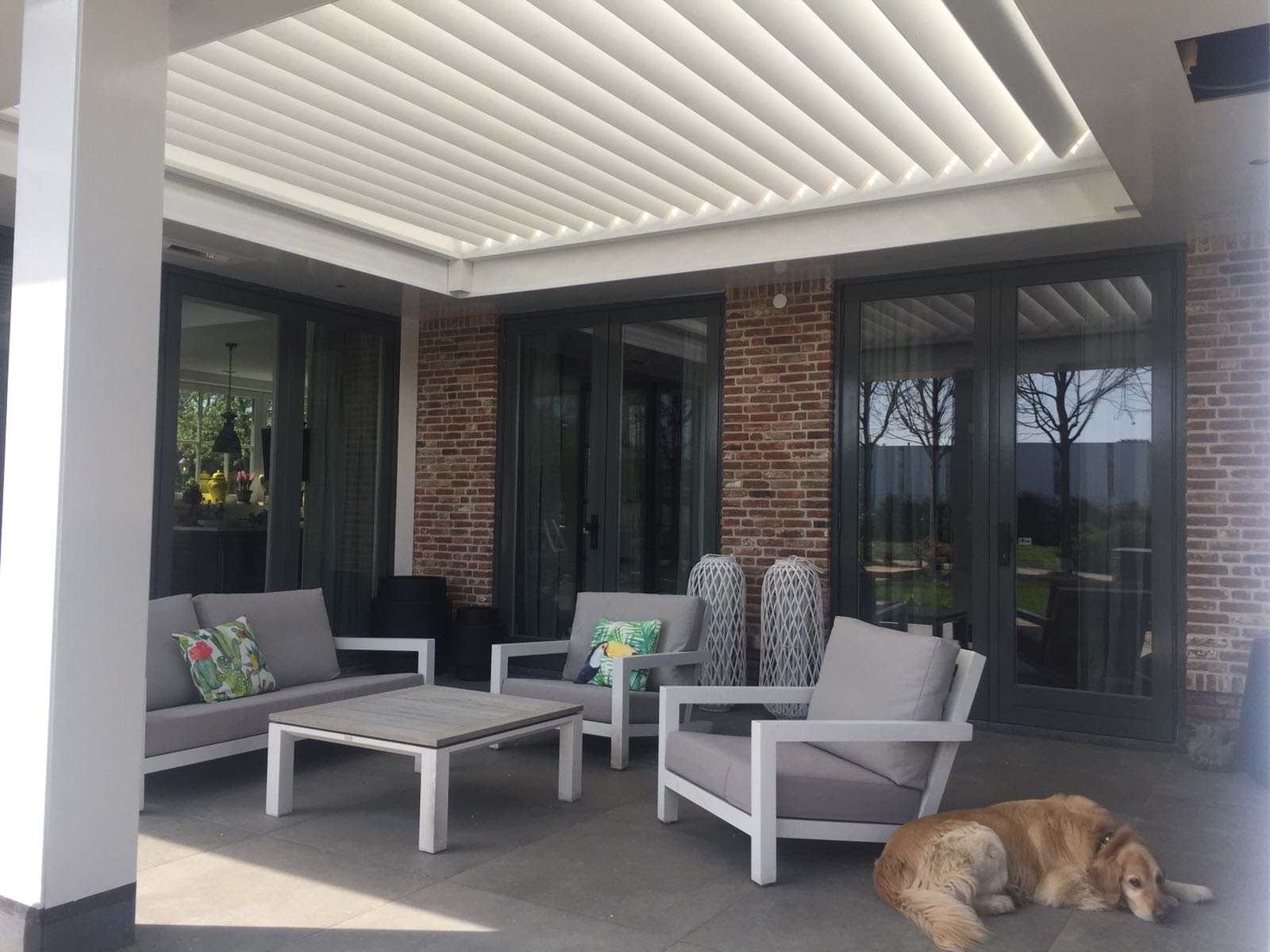 Het terras met een veranda met shutters zodat zowel in de zon als in de schaduw gezeten kan worden