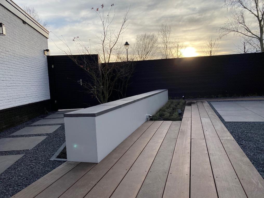 Betonlook muurtje met vlonder in tuin