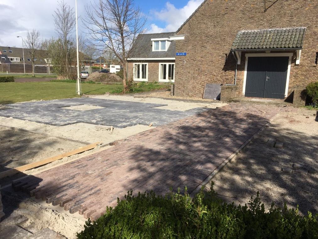 De aanleg van een klinkerpad en tegel terras