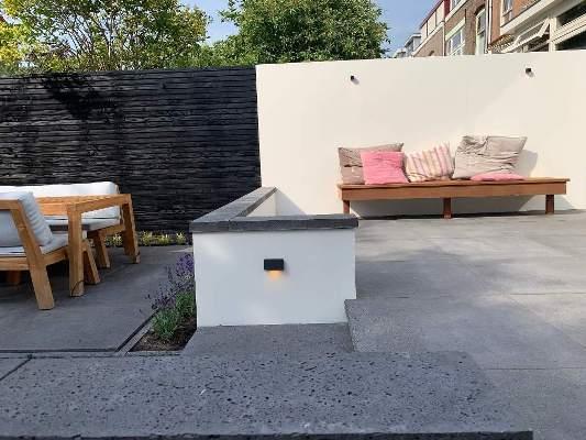Zwarte schutting met betonlook muur