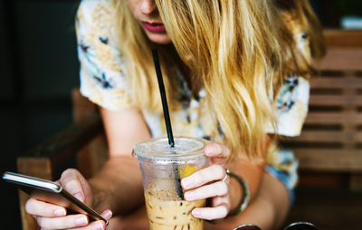 Mahnungen und Rechnungen aufs Smartphone - Junge Frau mit Smartphone und Eiskaffee in den Händen