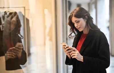 Mobile Coupons auf dem Smartphone - Junge Frau vor Schaufenster schaut aufs Handy