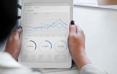 Online-Datenerhebung - Frauenhände mit Tablet, auf dem ein Dashboard mit Statistiken angezeigt wird