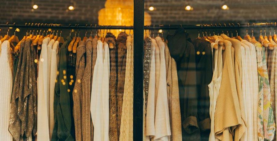 Kleider auf Stange im Geschäft. Kunde steigert Conversion Rate von Gutscheinen durch Mobile Coupons.