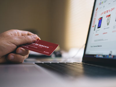 Hand mit Kreditkarte vor Laptop. Customer Loyalty dank Gutscheinen per SMS.