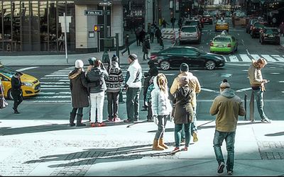 Menschen in der Stadt schauen aufs Handy. Immer mehr Unternehmen kontaktieren Konsumenten per SMS.