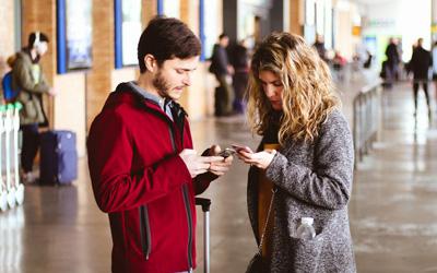 Zwei Personen tippen am Handy. Zahlreiche Branchen nutzen SMS als Kommunikationskanal zu ihren Endkunden.