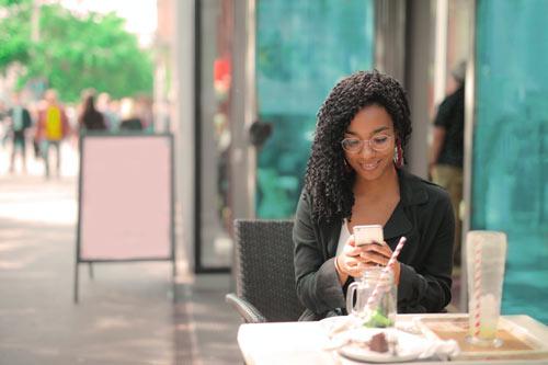 Frau mit Smartphone sitzt draußen im Café. Kunden jederzeit auf dem Handy erreichen. Mobile Marketing