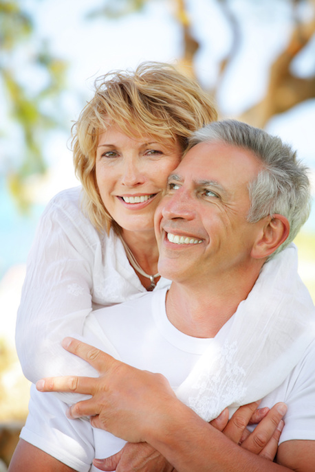 older couple at the beach smiling