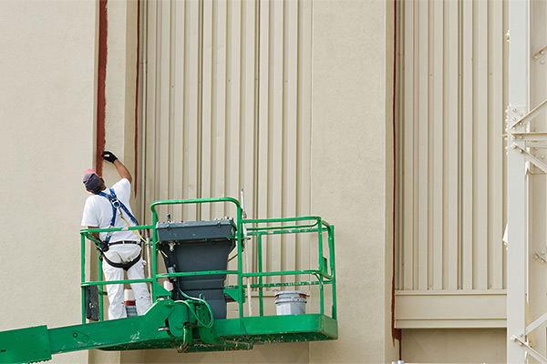 Man painting the side of a commercial building