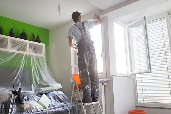 Man painting the interior of a bedroom